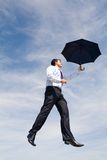 In the sky. Creative image of businessman with black umbrella flying on the background of sky Stock Images