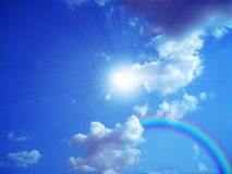 Sky. Bright sun and rainbow with white cloud on background blue sky Royalty Free Stock Images