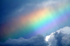 Sky ablaze. A partial very bright rainbow seen over the ocean Royalty Free Stock Images
