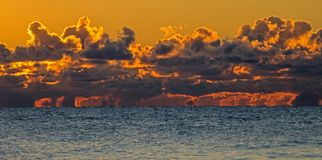 Sky Ablaze Over Lake Ontario At Toronto, Ontario, Canada. Cumulus Clouds bursting with bright colour at sunrise over Lake Ontario off the shore of Toronto royalty free stock photos