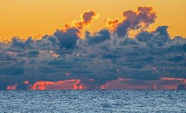 Sky Above Lake Ontario On Fire At Sunrise. Shoreline rocks, Lake Ontario and cumulus clouds seen from Etobicoke Point at Humber Bay Park West in Toronto, Ontario stock images