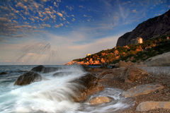 The sky above the resort of the Mediterranean Sea. Storm waves crash on a rock in the early morning on the ocean coast Stock Photo