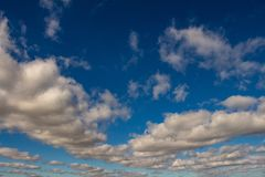 Sky of abundant white clouds and celestial spaces. Cottony clouds distributed throughout the sky royalty free stock photography