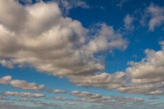 Sky of abundant white clouds and celestial spaces. Cottony clouds distributed throughout the sky stock photography