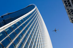 Sky, airplane and office building. An airplane flying over a business building stock photos
