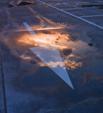 Sky arrow. Puddle reflecting sunset with arrow Royalty Free Stock Photo