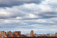 Sky with blue clouds over urban houses. Winter evening sky with blue clouds over urban houses Royalty Free Stock Image
