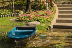 A sky-blue fiberglass boat on a lovely flower-trimmed pond in a Thai garden park. A sky-blue fiberglass boat on a lovely flower-trimmed pond in a garden park in Stock Photo