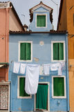 Sky blue little house in Burano with white sheets and clothes ha Royalty Free Stock Image