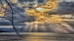 Sky breakthrough over the sea. With dark cloud and orange sun light, very amazing sky in the winter royalty free stock image