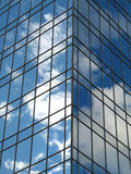 Sky building. Reflections of sky and clouds soften the exterior of this modern glass building Royalty Free Stock Image
