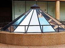 Sky and Building Reflections in Conical Glass Atrium. Modern architectural details with a small conical atrium with sky and building reflections in glass panels royalty free stock photography