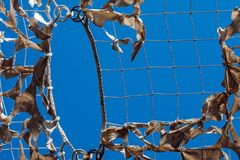 Sky camouflage net military torn light white blue shadow. White military mesh with torn holes with shadows from bright sunlight. Camouflage net and the blue sky Stock Image