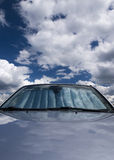 Sky car with sun screen. Sky reflected on the hood and windshield of a car with a sunscreen installed Royalty Free Stock Photos