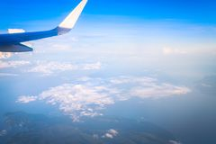 Airplane wing out of window. Sky and cloud as seen through window of an aircraft Royalty Free Stock Photos