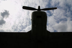Sky and cloud under head plane view, silhouette below front. Sky and cloud under head plane view with wing and paddle, silhouette below front Royalty Free Stock Images