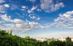 Sky with clouds on a background of trees and buildings. Sky with clouds with trees in the foreground and the buildings in the background summer in afternoon royalty free stock photography