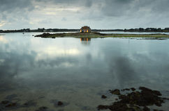 Sky with clouds and cottage reflected in the sea. Sky full of clouds and cottage reflected in the sea at dusk Royalty Free Stock Images