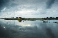 Sky of clouds and cottage reflected in the sea. Sky full of clouds and cottage reflected in the sea at dusk Stock Photo