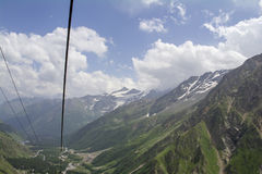 Sky in the clouds green and snow on the mountains and lift cable, North Caucasus Elbrus region. Royalty Free Stock Photos