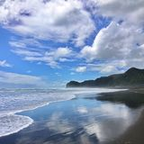Surf reflections at Piha beach New Zealand. Sky and clouds reflect off the dark wet sand as the surf rolls in at Piha beach in New Zealand royalty free stock photography