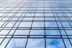 Sky and clouds reflected in symmetric mirrored facets of windows at modern office building - high quality texture / background stock photos