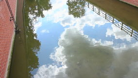 Sky and clouds reflection in water. Near the building stock footage