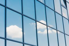 Sky and clouds reflection in the windows of. Modern skyscraper royalty free stock photo