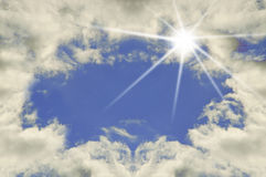 Sky with clouds and sun. This image shows a patch of blue sky surrounded by clouds and with a flash of  sun Royalty Free Stock Image