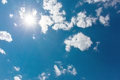 In the sky of the clouds, the sun has dazzling rays, sunny beautiful blue sky royalty free stock photo