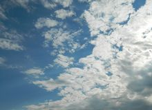 Sky with clouds and sun. This represents a beautiful sky with clouds, menacing to the left, but also sunny more to the right in contrast Stock Photos