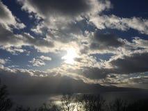 Sky clouds sun shining. Lake mountain sunshine Stock Image