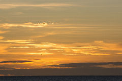 Sky and clouds at sunset. Beautiful orange sunset sky with small bird in silhouette Stock Photography