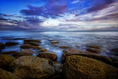 Winter day by the sea. The sky is cloudy. Sea waves are striking the shore. Ice on the rocks Stock Photos