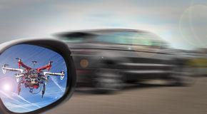 Sky cop drone. Photo of a speeding car with sky cop drone spotted in mirror chasing car stock photography