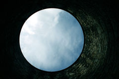 Sky copy space from bottom of well. A circular area of sky, looking like the moon, taken from the bottom of a stone column Stock Image