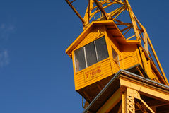 Sky Crane. An old yellow freight crane stands against a bright blue sky royalty free stock photo