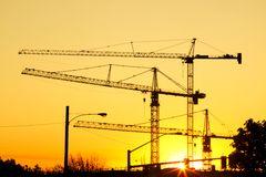 Sky Cranes. Huge sky cranes at a construction site silhouetted against a setting sun Stock Photography