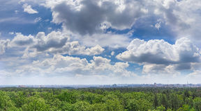 Sky with cumulus clouds over forest and modern city Royalty Free Stock Photography