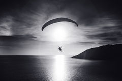 Sky diver flies at sunset over the bay. Black and white photo Royalty Free Stock Images