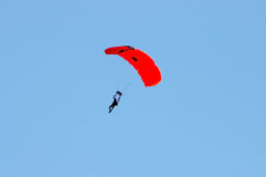 Sky Diving 2. A skydiver with a red parachute against the blue sky Royalty Free Stock Image