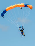 Sky diving tandem parachutists gliding toward landing Stock Images