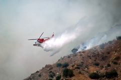 Sky Diving Water Dropper. Helicopter fighting forest fire by diving down to do water drop Stock Photo