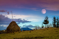 Romania.Transylvania.Bran village.Sky at dusk and full moon in the countryside. Transylvania, Romania.a haystack on a twilight sky with a full moon background Stock Photo