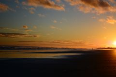 Dramatic sunrise colours; beautiful sunrise on a beach and a lonely figure of a person walking along the beach. stock image