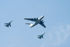Sky escort. Two fighters escort the transport plane royalty free stock photos