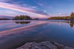 Sky feathering. Beautiful sunrise in uninhabited place. Pink clouds that look like giant pink feathering are reflected in Ladoga lake, located in Karelia, north Royalty Free Stock Photography