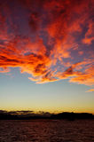 The sky is on fire. Dramatic evening sky, red clouds, blue and yellow sky, dark water Royalty Free Stock Images