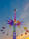 Sky Flyer. People sitting suspended from an amusement park ride as it spins them above the crowds at the Wisconsin State Fair Royalty Free Stock Image