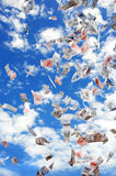Sky full of money. Flying papermoney in the blue sky stock photography